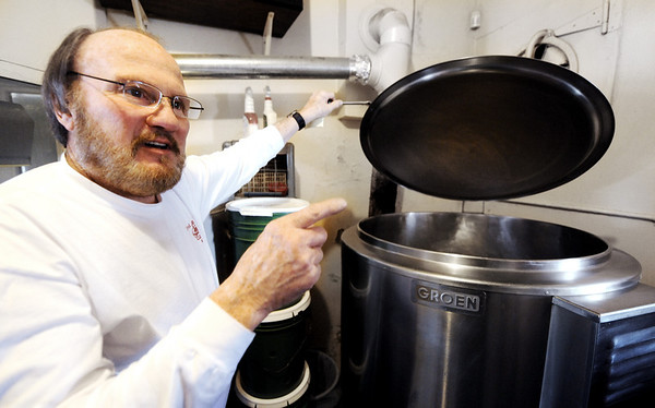 Globe/T. Rob Brown<br /> Larry Wilcoxson, owner of Fred 'n' Red's, talks about the large pot the Joplin business cooks has cooked chili in for many years.