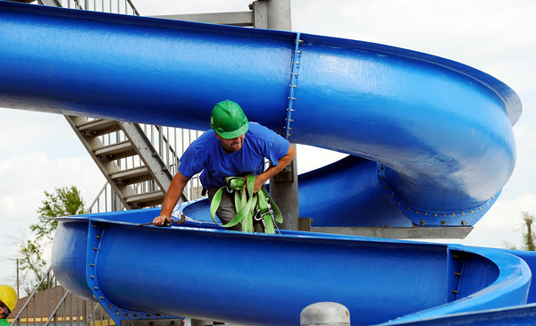 """Globe/T. Rob Brown<br /> Jereme Glenn, a caretaker with Joplin Parks & Recreation, maneuvers down a new water slide during installation Wednesday afternoon, March 28, 2012, at Cunningham Park Pool. This 16-foot-tall and 40-foot-long slide was donated by the city of Fort Scott, Kan., as part of the Joplin tornado recovery efforts. In addition, the city of Joplin is installing a 28-foot-tall, four-flume slide. """"This is going to be the pool to be at this summer,"""" said Chris Cotten, Joplin Parks director. """"We're real excited. It's going to come together nicely."""" Cotten said the aquatic center will also feature a new toddler play area with a miniature slide, water cannons, climbing nets, dumping bucket and more. Also, the rebuilt building now has hurricane straps, metal tie-downs and reinforced walls."""