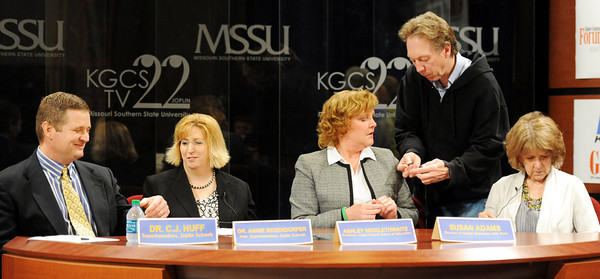Globe/T. Rob Brown<br /> Bill Hunt, KGCS director of creative services, affixes a microphone on Ashley Micklethwaite, Joplin Board of Education president, Wednesday afternoon, March 28, 2012, at MSSU's KGCS TV 22 studio. Panel members, pictured from left, are: Dr. C.J. Huff, superintendent; Dr. Angie Besendorfer, assistant superintendent; Micklethwaite; and Susan Adams, human resources director.