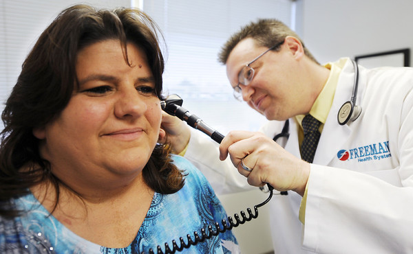 Globe/T. Rob Brown<br /> Susan Robinson, of Carl Junction, patiently waits as Dr. Keir Neighmond, family medicine at Freeman Health System, examines her ears during Robinson's checkup Thursday afternoon, March 8, 2012. Robinson has been undergoing medical treatment due to mold that resulted from the May 22, 2011, tornado.