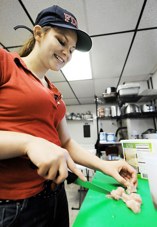 Globe/T. Rob Brown<br /> Employee Bailey Young, 15, of Carl Junction, slices alligator meat at Johnboat Caf'e in Duenweg, Wednesday afternoon, March 21, 2012.