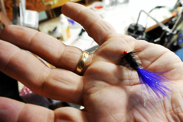 Globe/T. Rob Brown<br /> Tim Homesley, master angler and owner of Tim's Fly Shop near Roaring River State Park near Cassville, hold out a fly he tied Thursday afternoon, March 2, 2012.