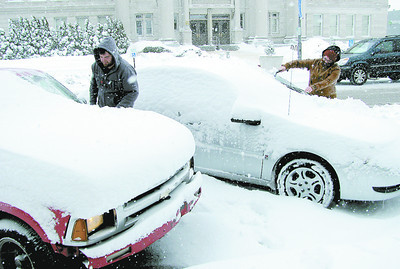 Martin Gorham (left) and Hailey Twitty dig out their vehicles on Lebanon's square Monday morning.