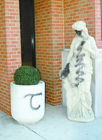 Police believe the person who vandalized this statue and planter at the Key Bank building in Lebanon is the same person who spray painted the Boone County Courthouse, the Lebanon Public Library, and other buildings.