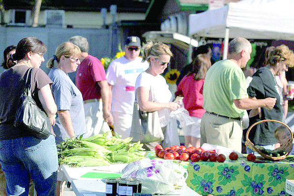 Shoppers peruse the offerings at the Zionsvile Farmers' Market in August last year.