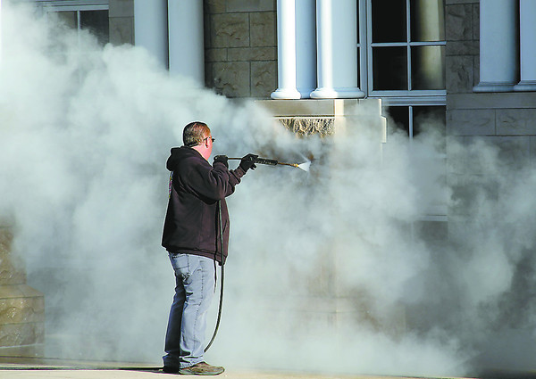 John Reed of Pioneer Restoration power-washes spray paint from a pillar at the Lebanon Public Library Thursday.