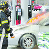 "Reporter photo by rod rose<br /> Lebanon firefighter Rodney Princell waits for water at a car fire Friday morning at the Speedway station on North Lebanon Street. The driver, Rebecca Saulmon, and her 18-month-old child escaped unharmed. Rebecca called her father, Dave Saulmon, and told him she ""smelled something"" and pulled into the station to find smoke coming from the engine compartment. ""I just put new tires on it,"" Dave Saulmon said. A broken fuel line was believed to be the source of the fire. LFD Deputy Chief Mike Baird said Speedway employees shut off the gas pumps as a precaution."