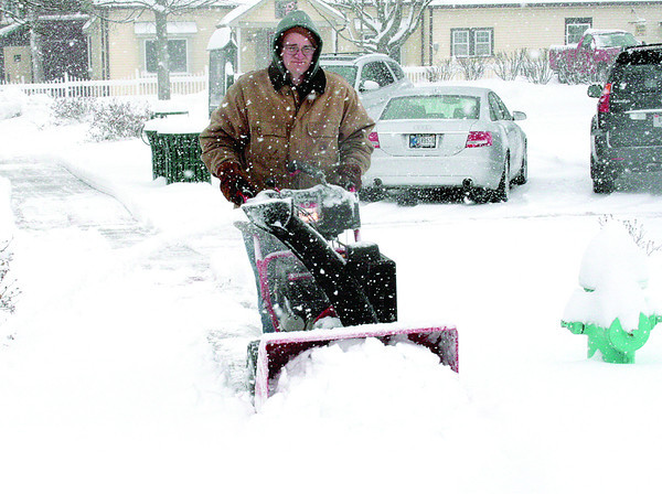 Jeff Bennington, with the Zionsville Department of Parks and Recreation, clears a sidewalk Monday morning, March 25, along Main Street.