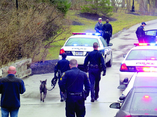 Officers from Zionsville and Carmel police departments use a tracking dog Monday morning, March 11, to search for two African American male suspects near the Longbrook subdivision. The two males fled the scene after robbing the Key Bank on Michigan Road. The two suspects are still at large.