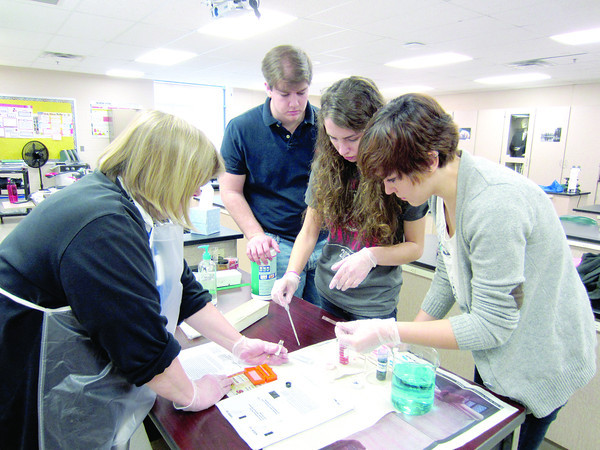 "AP Biology students prepare slides with CeLa cells. These are special cells that originally came from a cancer that Henrietta Lacks had as portrayed in the book ""The Immortal Life of Henrietta Lacks."" As part of a grant from the Zionsville Education Foundation and the Zionsville PTO, the students read the book, the cells were ordered from the American Institute of Cancer Research and the students were able to prepare the slides and study the cells under a microscope. Pictured are teacher Lori Bing, Austin Brewer, Miranda Meade and Audrey Todd."