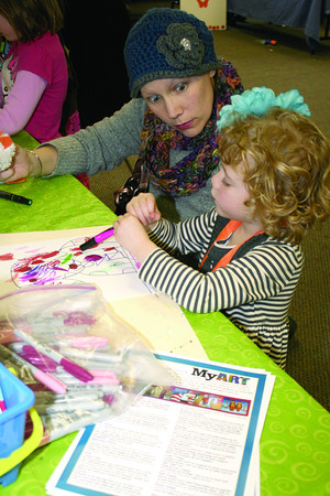 Four-year-old Reese Rosbottom draws a dog at Nature Fest Saturday, March 1. Her mom, Megan Rosbottom, holds a chick Reese made at another booth as she watches her daughter finish her drawing project at the MyArt studios booth. The annual Nature Fest event was held at Zionsville Town Hall.