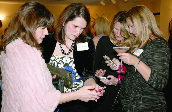 "From left, Chelle Smitson, Andi Hardesty, Greta Cline and Amy David have a quick lesson on online bidding for the silent auction at the Zionsville Education Foundation's Girls Night Out. The event, themed ""Getaway"" and held at The Palamino Ballroom Friday night, Feb. 28, replaces the annual spring style show and luncheon. Funds raised will support ZEF's fall grant program."