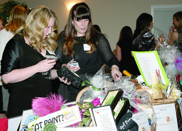 "Stephanie Armbrester and Grace Fletcher look over silent auction items at the Zionsville Education Foundation's spring fundraiser Friday night, Feb. 28, at the Palamino Ballroom. The usual spring style show and luncheon was made over into Girls Night Out with the theme ""Getaway."" Funds raised at the event will support ZEF's fall grant program."