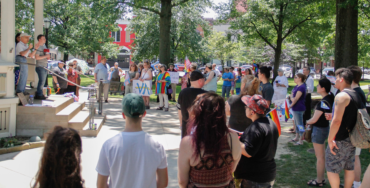 ALEC SMITH / GAZETTE  Greg Coleridge (upper left, with microphone) speaks Sunday at Medina's Public Square to an audience of about 100 who attended a rally for Medina-based OutSupport, an advocacy group for lesbian, gay, bisexual and transgender individuals.