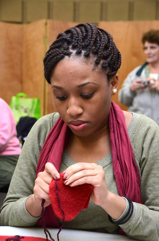 . MCLA sophomore Sherley Jules, sews mittens for children in the North Adams Public Schools and Northern Berkshire Headstart, during the 2014 MLK Jr. \'Day of Service\' at the MCLA Church Street Center on Monday, Jan. 20, 2014.  (Gillian Jones/Berkshire Eagle Staff)