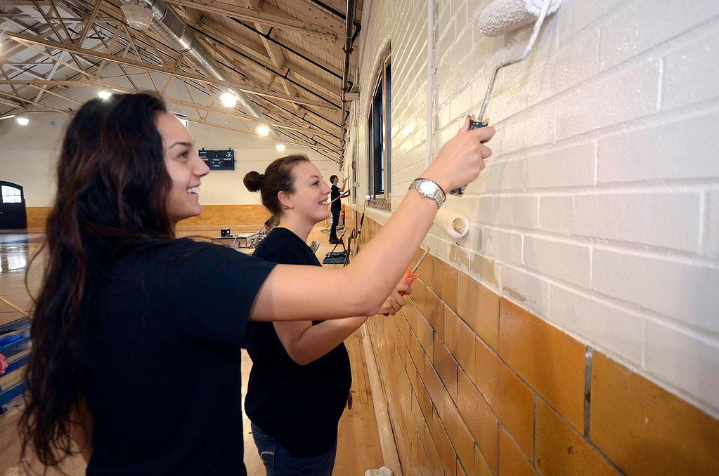 . Rachel Mills and Amanda Fleming, members of the MCLA womens\' volleyball team, paint the walls of the North Adams Armory during the 2014 MLK Jr. \'Day of Service\' on Monday, Jan. 20, 2014.(Gillian Jones/Berkshire Eagle Staff)
