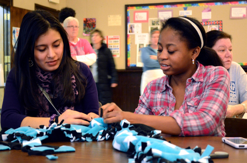 . BCC students Kimberly Figueroa and Esperance Behanzin make scarves at the First United Methodist Church as part of a Martin Luther King Jr. \'Day of Service.\'  The scarves were given away at a lunch held in honor of Dr. King at the church.on Monday, Jan. 20, 2014.  (Ben Garver / Berkshire Eagle Staff)
