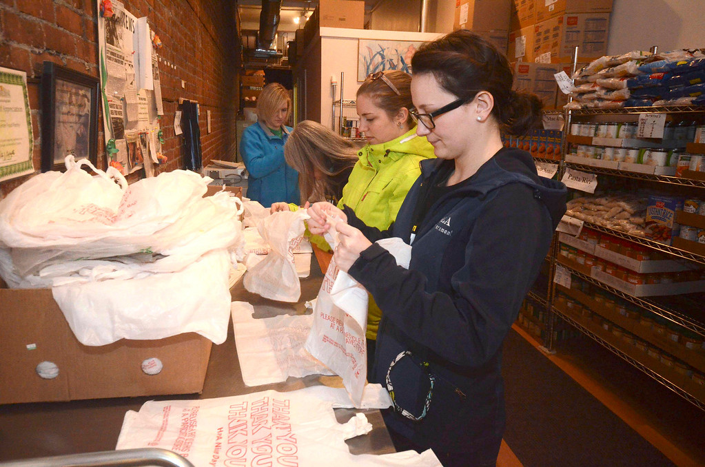 . MCLA sophomores Emily O\'Toole and Alexandra Kadell open plastic bags to hold food at The Friendship Center Food Pantry on Eagle Street in North Adams, during the 2014 MLK Jr. \'Day of Service\' on Monday, Jan. 20, 2014. (Gillian Jones/Berkshire Eagle Staff)