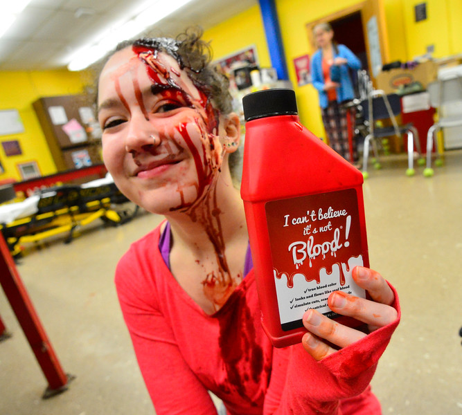 "KRISTOPHER RADDER - BRATTLEBORO REFORMER<br /> Sage Hall, a senior at Leland & Gray Union Middle and High School, holds a bottle of ""I Can't Believe It's Not Blood."""