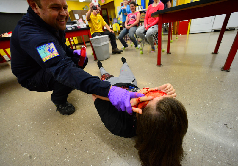 KRISTOPHER RADDER - BRATTLEBORO REFORMER<br /> Rescue Inc. Operations Chief Drew Hazelton has some fun with Nastia Stevens, a senior at Leland & Gray Union Middle and High School, while smearing fake blood across her face during a school bus crash mass casualty drill on Wednesday, May 16, 2018.