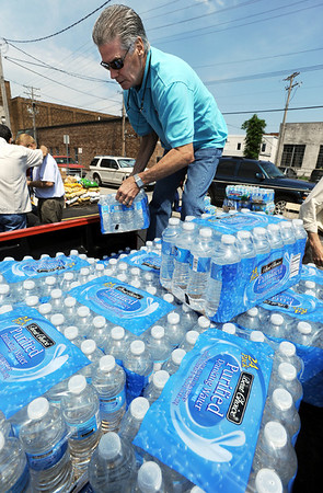 Globe/T. Rob Brown<br /> Daniel Sweeney, of Tulsa, Okla., a member of Believers Church, stacks cases of water into the back of a pickup truck Friday morning, May 27, 2011, in the parking lot of Central Christian Church in downtown Joplin. The bottled water is being transported around town for anyone in need and emergency responders.