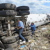 Globe/T. Rob Brown<br /> Steve Baker, co-owner, and David Hayes, both with Baker's Towing Service, add chains to attach a wench to, in an attempt to turn over a 9-ton propane truck that was thrown across a lot by Sunday's tornado, on Thursday afternoon, May 26, 2011, in order to salvage what they can.