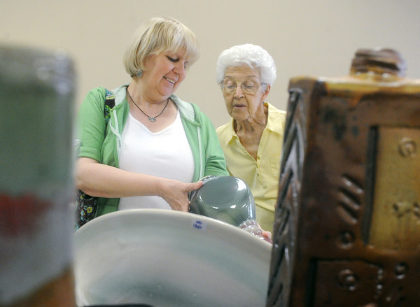 Globe/Roger Nomer<br /> Debbie Pryor, left, Columbus, and Gladys Tuggle, Webb City, look over a clay vase crafted by Netti Curtis at the Midwest Artists Clay Show and Sale at the City Pointe Shopping Center in Webb City on Saturday.  The sale continues on Sunday from noon to 4:00 p.m.