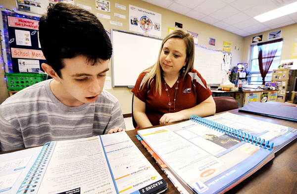 Globe/T. Rob Brown<br /> Kaleb Hansen, 14, a Joplin South Middle School student with autism, works on a class language arts assignment with teacher Tashena Vickers Wednesday afternoon, May 2, 2012. Hansen's reading level has been rapidly increasing.