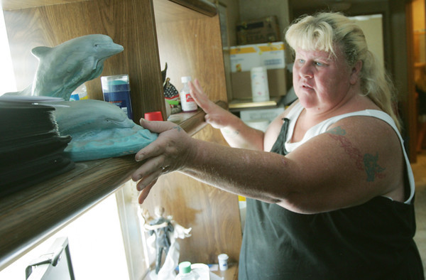 Globe/Roger Nomer<br /> Terri Martin prepares to pack a dolphin statue at her FEMA trailer on Wednesday afternoon.