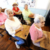 Globe/T. Rob Brown<br /> To the front of the class--Cave Springs School's, from left, Pat Beasley, of Carl Junction, Jan Whitworth, of Joplin, Wanda Tackett, of Stott City, Helen Hunter, of Carthage, and Betty Still, of Carthage, sit in the antique desks Thursday morning, May 10, 2012, of the school house where most of them attended. Beasley, Whitworth, Hunter and Still are all sisters who grew up in the Cave Springs area, just north of Sarcoxie.