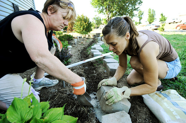 Globe/T. Rob Brown<br /> Lynda Williams, left, and her future daughter-in-law, Jennifer Bridge, both of Joplin, help rebuild the castle wall around Williams' flower garden Wednesday afternoon, May 30, 2012, near the intersection of East 15th Street and Massachusetts. Williams' garden was destroyed during the May 22, 2011, tornado.