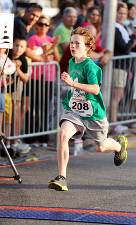 Globe/T. Rob Brown<br /> Jonathan St. Clair, 12, of Joplin, comes across the finish line of the kids 1-mile run to win the event Saturday morning, May 19, 2012, during the Joplin Memorial Run in downtown Joplin.