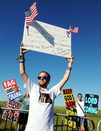 Globe/T. Rob Brown<br /> Jamey Johnston, of Chicago, who helped Joplin rebuild as part of Americorps, holds up a sign in protest of the Westboro Baptist Church protestors (background) Monday afternoon, May 21, 2012, at Missouri Southern State University. The Westboro group was protesting Joplin, Obama, and homosexuality.