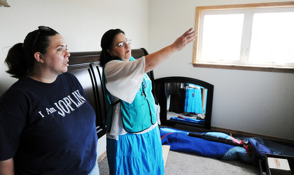 Globe/T. Rob Brown<br /> Catholic Charities case manager Norma Hernandez speaks with home owner Amy Jump as work continues on the Jump family home Tuesday morning, May 8, 2012, in Joplin.