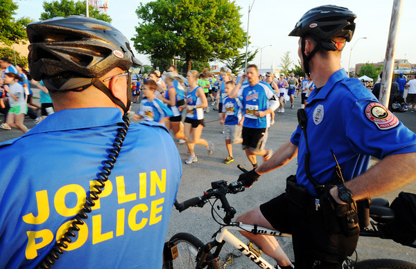 Globe/T. Rob Brown<br /> Joplin Police officers Cpl. Brian Henderson, left, and James Kelly watch runners during the half-marathon run Saturday morning, May 19, 2012, during the Joplin Memorial Run in downtown Joplin.