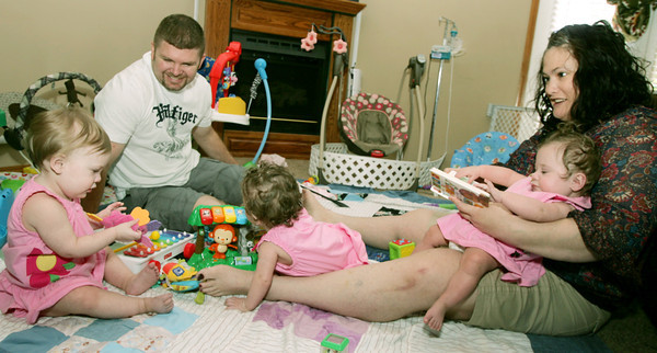 Globe/Roger Nomer<br /> Chris and Jayme Harper play with their triplets (from left) Reagan, Addison and Lauren on Thursday morning.  The girls turned one year old yesterday.