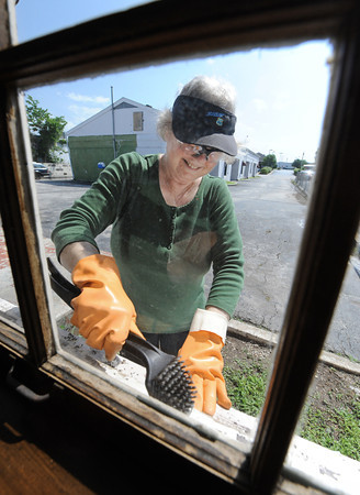 Globe/T. Rob Brown<br /> Barbara Hart, of Carthage, one of the property managers for the Boots Motel in Carthage scrapes the paint off a window sill Tuesday morning, May 1, 2012, at the Route 66 landmark.