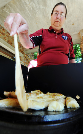 Globe/T. Rob Brown<br /> Billie Mullins, of rural Joplin, sautés butter and brown sugar over bananas to make scrumptious banana dump cobbler on a dutch oven lid at the Isaac Walton League Lodge in the Walter Woods Conservation Area south of Joplin.