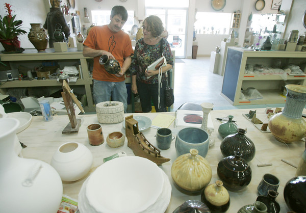 Globe/Roger Nomer<br /> Brent Skinner shows Dayan Edwards a pottery piece at Phoenix Fired Arts on Thursday morning.