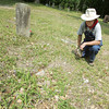 Globe/Roger Nomer<br /> Jim Van Fleet examines a sunken gravesite at Miller Cemetery on Thursday.