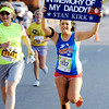 Globe/T. Rob Brown<br /> Jody Kirk, of Silver Creek, holds up a sign in memory of her father, Stan Kirk, who died during the May 22, 2011, tornado as she nears the finish line for the 5K run Saturday morning, May 19, 2012, during the Joplin Memorial Run in downtown Joplin.