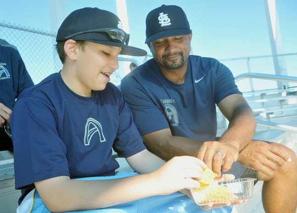 Globe/Roger Nomer<br /> Tony and Sam, 13, Dattoli, St. Louis, enjoy nachos at the Joplin Athletic Complex during the NJCAA Region XVI Baseball tournament on Wednesday afternoon.  Dattoli is the head coach of the St. Louis Community College baseball team.