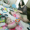 Globe/Roger Nomer<br /> Reagan and Lauren play with their mother Jayme on their birthday Thursday.