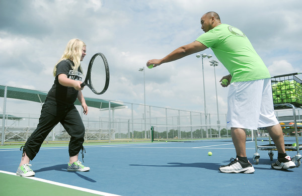 Globe/Roger Nomer<br /> Matt Sombito helps Scout Crow, 8, with her tennis swing at the Joplin Tennis Complex during Tennis Day events on Saturday.  The complex offered games and prizes to help teach kids the game of tennis.