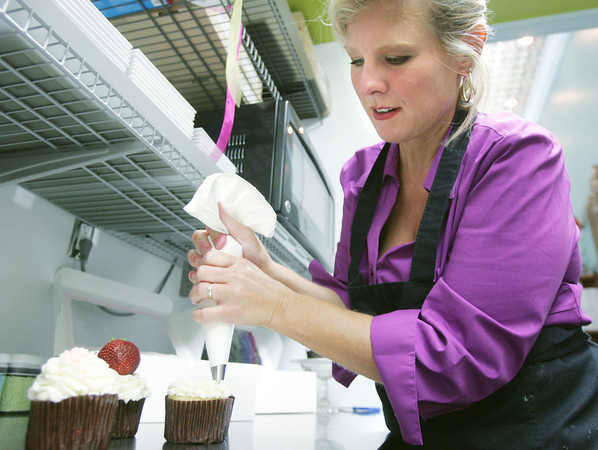 Globe/Roger Nomer<br /> Liz Easton decorates a cupcake at the new kitchen in Cupcakes by Liz on Thursday morning.
