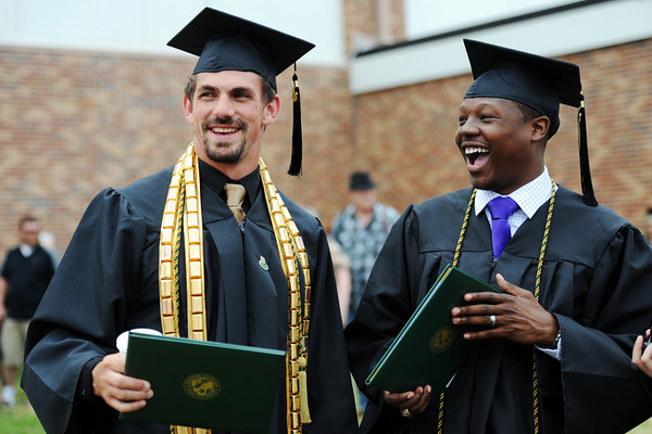 Globe/T. Rob Brown<br /> College graduates Dusty Bratzler, left, elementary education and special education major, and T.J. Williams, general studies major, both of Tulsa, Okla., and both MSSU athletes, share a laugh as they celebrate outside MSSU's Leggett & Platt Athletic Center following the first session of commencement exercises Saturday morning, May 19, 2012.