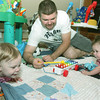 Globe/Roger Nomer<br /> Chris Harper plays with Reagan, left, and Addison on the triplets' birthday.
