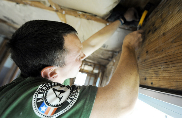 Globe/T. Rob Brown<br /> Team leader Jeff Leininger, of Chapel Hill, N.C., with Americorps NCCC of Denver, hammers in a hurricane tie to a house Monday afternoon, May 21, 2012, in the 2600 block of West 32nd Street in Joplin. The home was severely damaged during the May 22, 2011, tornado.