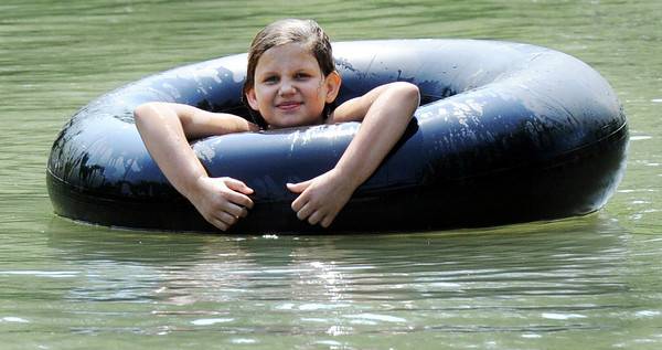 """Globe/T. Rob Brown<br /> Hailey Gordon, 10, of Carl Junction, """"steals"""" a friend's inner tube for a lazy creek ride Friday afternoon, May 25, 2012, at the Stone's Corner Public Fishing Access, Missouri Conservation Department, on North Main Street/43 Highway, for Center Creek."""