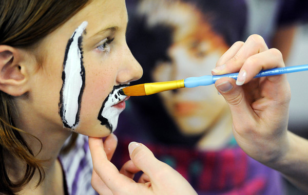 Globe/T. Rob Brown<br /> Sidney Napier, 7, of Joplin, holds still as the hands of April Miller, volunteer of Carthage, paints her face under the watchful eye of a Justin Bieber T-shirt Wednesday afternoon, May 16, 2012, at the Joplin Boys & Girls Club.